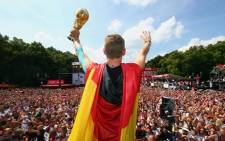 German star Bastian Schweinsteiger waves to the crowd on Berlin's 'Fan Mile' with the World Cup trophy in his hand. Picture: Official DFB Facebook Page.