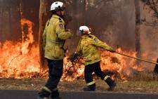 Firefighters conduct back-burning measures to secure residential areas from encroaching bushfires in the Central Coast, some 90-110 kilometres north of Sydney on 10 December 2019. Picture: AFP
