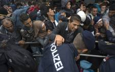 FILE: Hundreds of migrants struggle to board a train on 11 September, 2015 at a train station in Nickelsdorf, at the Austrian side of the border between Hungary and Austria. Picture: AFP.