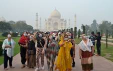 Foreign tourists wearing face masks visit the Taj Mahal under heavy smog conditions, in Agra on 4 November 2019.  Picture: AFP