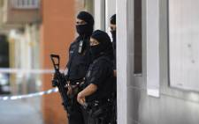 Catalan regional police (Mossos d'Esquadra) forces stand guard outside the apartment building of a man who tried to attack a police station in Cornella near the northeastern Spanish city of Barcelona on 20 August 2018. Picture: AFP.