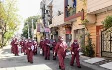 FILE: Medical staff wearing protective gears walk in a residential area to screen residents in the wake of COVID-19 coronavirus outbreak, during a government-imposed nationwide lockdown as a preventive measure against the COVID-19 coronavirus in Amritsar, India, on 12 April 2020. Picture: AFP.