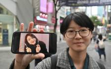 FILE: This picture taken on 10 October 2019 shows South Korean woman Yoon Ji-hye displaying an old photo of herself during an interview with AFP at the Myungdong shopping district in Seoul. Picture: AFP