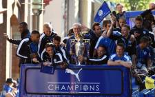 FILE: Leicester City's Italian manager Claudio Ranieri (C) holds the Premier league trophy as the Leicester City team take part in an open-top bus parade through Leicester to celebrate winning the Premier League title on 16 May, 2016. Picture: AFP.