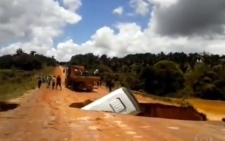 A screengrab from a video showing Brazilian tour bus being washed away in a muddy river.