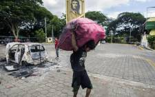 """A scavenger carries cables and metal collected from burnt cars and the """"national rural cash savings and credit cooperative"""" (CARUNA) building, set on fire Wednesday night by anti-government demonstrators during a march to mark Mother's Day, on 31 May, 2018. Picture: AFP."""