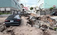 A car is seen stuck on a road damaged by an earthquake in Sapporo, Hokkaido prefecture on 6 September 2018. Picture: AFP.