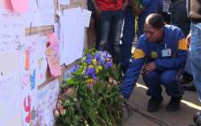 A Tshwane SAPS Academy student adds flowers to the wall of messages and well wishes for Madiba at the entrance of the Pretoria Heart Hospital.  Picture: Christa van der Walt/EWN.