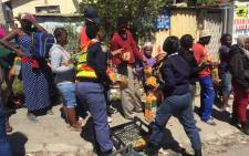 SAPS officials handing out bread and other food items to residents queuing to register their names at the community hall following deadly fire in Imizamo Yethu. Picture: Kevin Brandt/EWN.