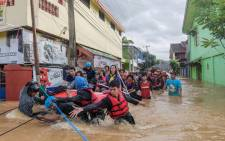 This picture taken on 23 January 2019 shows residents evacuating their homes in Makassar as heavy rain and strong winds pounded the southern part of Sulawesi island, swelling rivers that burst their banks and inundating dozens of communities in nine southern districts. Picture: AFP