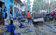 People stand among damages at the scene of a blast after two car bombs exploded in Mogadishu on 28 October 2017. Picture: AFP.