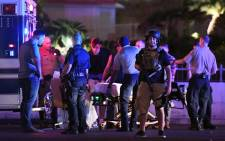 Police officers stand by as medical personnel tend to a person on Tropicana Ave. near Las Vegas Boulevard after a mass shooting at a country music festival nearby on 2 October 2017 in Las Vegas, Nevada. Picture: AFP.