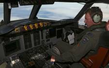 FILE: Royal New Zealand Air Force P3 Orion co-pilot Squadron Leader Brett McKenzie flies the plane while searching for missing Malaysia Airlines flight MH370, over the Indian Ocean on 31 March, 2014. Picture: AFP.