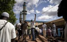 On 12 July 2020 protesters gesture on a barricade put up in front of the Salam mosque of Badalabougou, where the influential Imam Mahmoud Dicko led a prayer dedicated to the victims of the clashes of the past two days in Bamako. Picture: AFP
