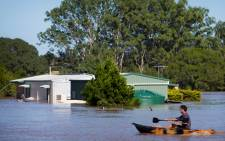 A resident uses a kayak to paddle past a house, partially submerged under floodwaters caused by Cyclone Debbie, to rescue a stranded cow on his property in North MacLean, Brisbane on 1 April 2017. Picture: AFP.
