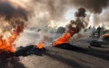 Tyres burning on the street of Ennerdale, south of Johannesburg, during a protest against crime, drugs, unemployment and a lack of infrastructure development. Picture: EWN