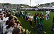 Relatives of the members of the Chapecoense Real football club team killed in a plane crash in Colombia enter the field during a funeral ceremony at the stadium in Chapeco, Santa Catarina, southern Brazil, on 3 December, 2016. Picture: AFP.