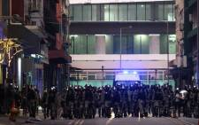 Riot police march in formation down a street in Hong Kong's Kwun Tong district on 24 August 2019. Picture: AFP