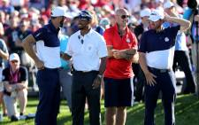 Dustin Johnson of the United States speaks to vice-captain Tiger Woods during singles matches of the 2016 Ryder Cup at Hazeltine National Golf Club on 2 October, 2016 in Chaska, Minnesota. Picture: AFP.