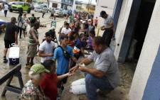 Hundreds of people line up to buy ice at a local plant in the aftermath of Hurricane Maria, in Arecibo, Puerto Rico, on 30 September 2017. Picture: AFP.