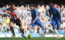 Chelsea's Spanish midfielder Juan Mata (C) shoots past Brentford's Harlee Dean (L) to score the opening goal of the English FA Cup fourth round replay football match between Chelsea and Brentford in London on February 17, 2013. Picture: AFP/OLLY GREENWOOD