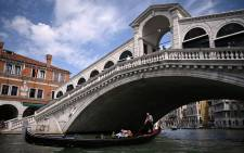Tourists go for a gondola ride by the 16th-century stone arch Rialto Bridge at the Grand Canal in Venice on 7 September 2021 as part of an inauguration ceremony after the bridge underwent major restoration. Picture: Marco BERTORELLO/AFP