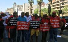 Cosatu members hold up posters during a strike for decent work on Friday 7 October 2016. Picture: Gia Nicolaides/EWN.