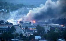Firefighters douse the blaze after a freight train loaded with oil derailed in Lac-Megantic in Canada's Quebec province on 6 July, 2013, sparking explosions that engulfed about 30 buildings in fire. Picture:EWN