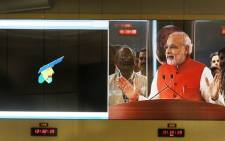 Indian Prime Minister Narendra Modi is seen on a screen as he addresses scientists alongside a graphic of the Mars Orbiter Spacecraft (MoM), after the spacecraft successfully entered into the Mars orbit, at the Indian Space Research Organisation's (ISRO) Telemetry, Tracking and Command Network (ISTRAC) in Bangalore on 24 September, 2014. Picture: AFP.