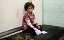 FILE: An injured child waits after receiving treatment at the University hospital in a government-held neighbourhood following reported rebel fire on government-held parts of the northern city of Aleppo. Picture: AFP.