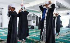 This picture taken on 22 May 2019 shows religious Muslim students adjusting their turban before observing Nuzul Quran, when the beginnings of the Koran were revealed to the Prophet Mohammed, in a mosque in Bentong. Picture: AFP