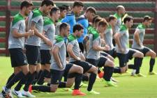 FILE: Australian Socceroos players go through their stretching exercises before a team training run in Victoria on June 11, 2014, as they prepare for the 2014 Fifa World Cup in Brazil. Picture: AFP.
