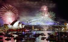 Fireworks light up the sky over Sydney's Opera House (L) and Harbour Bridge during New Year celebrations in Sydney on 1 January 2016. Picture: AFP