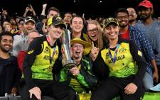 FILE: Australia's Rachael Haynes (L) and Ashleigh Gardner (R) cleberate with the trophy after winning the Twenty20 women's cricket World Cup final between Australia and India in Melbourne on 8 March 2020. Picture: AFP.