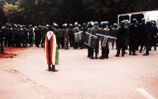 FILE: A man draped in Zimbabwean flag stands near police officers. Picture: Micaela Hamilton.