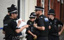 Police officers gather on a street near a property that they raided in the Moss Side area of Manchester on 27 May 2017. Picture: AFP