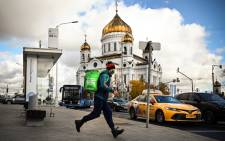 A food delivery courier wearing a protective mask runs in front of Christ the Saviour cathedral, the main Russian Orthodox church in central Moscow, on 18 October 2021. Picture: Alexander NEMENOV/AFP