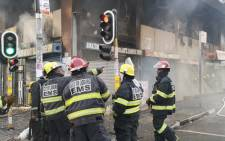 Firefighters attend to a burning building on the corner of De Villiers and Rissik street in Johannesburg. Picture: EWN
