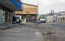 A man walks towards a looted shop as police watch on after protests in Coligny in the North West over the death of a young boy. Picture: Reinart Toerien/EWN