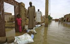 FILE: Sudanese residents walk on sandbags to reach their houses along a flooded street in the capital Khartoum's southern neighbourhood of al-Kalakla, on 31 August 2020. Picture: AFP.