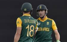 South African batsman Faf du Plessis (L) speaks to teammate AB de Villiers (R) after he was dismissed by New Zealand during the Cricket World Cup semi-final match between New Zealand and South Africa at Eden Park in Auckland on 24 March, 2015. Picture: AFP.