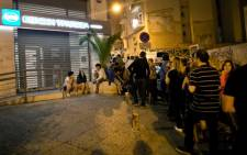 FILE: People queue in front of an ATM to withdraw cash from a National Bank of Greece in central Athens on 28 June 2015. Picture: AFP.