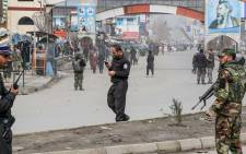 Afghan security forces personnel stand guard on a road near the site of a gun attack that occurred during an event ceremony to mark the 25th anniversary of the death of Shiite leader Abdul Ali Mazari, in Kabul on 6 March 2020. Picture: AFP