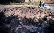 "Men walk past a bomb hole in а street after an ""air strike"" overnight in Donetsk, on 6 August 2014. Picture: AFP."