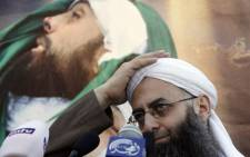 Lebanese Salafist figure Sheikh Ahmad al-Assir gestures in front of a picture of slain supporter Lubnan al-Azzi during a protest against the Syrian regime in the southern Lebanese city of Sidon on 2 December 2012. Picture: AFP.