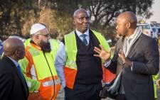 Minister of Transport Joe Maswanganyi talks to Gauteng MEC of Transport Ismail Vadi and Sanral CEO Skhumbuzo Macozoma. Picture: Thomas Holder/EWN.
