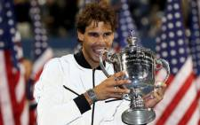 Rafael Nadal bites the US Open trophy as he celebrates winning the men's singles final match against Novak Djokovic of Serbia on 9 September 2013. Picture: AFP