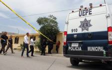 Forensic experts and policemen arrive at the crime scene, after the bodies of eleven people were found inside a house in Ciudad Juarez, State of Chihuahua, Mexico, on 3 August 2018. Picture: AFP
