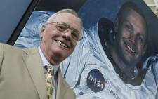 Astronaut Neil Armstrong poses in front of his photo during a visit to the Prince Felipe Museum, in Valencia on 26 July, 2005. Picture: AFP.