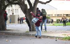 A student throws a rock at police as they clash outside the university. Photo: Bertram Malgas/EWN.